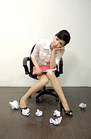 Businesswoman sitting near crumpled paper balls
