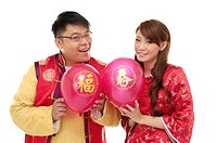Couple holding balloons and smiling