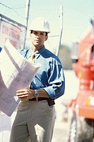 Portrait of a foreman standing at a construction site holding a blueprint