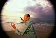 Side profile of a senior man practicing tai chi on the beach