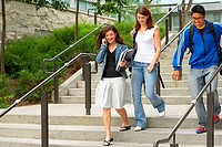 Three college students moving down a staircase