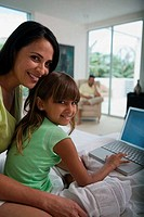 Girl using a laptop with her mother sitting behind her