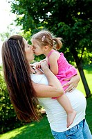 Pregnant woman kissing her daughter