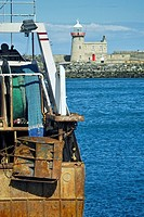 The Otter board and trawl nets of a trawler alongside the quay at Howth Harbour, with the East Wall lighthouse in the background, Howth, Co. Dublin, I...