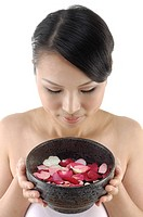 Close_up of a woman holding a bowl containing rose petals