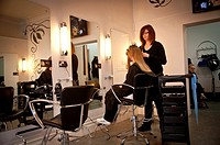 A young woman stylist cutting a teenage girl's hair in a hairdressing salon, UK