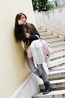 Attractive young woman is talking on a cellular phone on a staircase, surprised