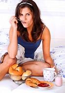 Brunette woman having breakfast in bed