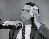 Close_up of a businessman wiping his face with a handkerchief