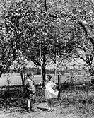 Vintage photograph of boy talking to girl standing with swing under trees in blossom