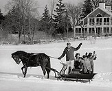 Mature couple with their children riding in a horsedrawn sleigh and waving their hands