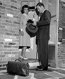 Insurance agent talking to young housewife at front door