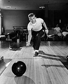 Teenage boy bowling