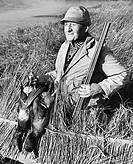 Male hunter holding two dead ducks and a rifle in a field