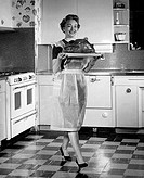 Young woman in the kitchen carrying a roasted turkey