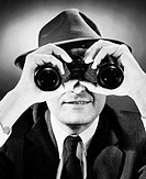 Close_up of a businessman looking through binoculars
