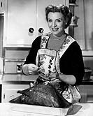 Portrait of a mature woman preparing a turkey in the kitchen