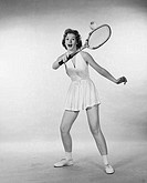 Young woman hitting a tennis ball with a tennis racket