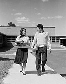 Teenage couple walking from school with books and smiling