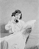 Teenage girl using telephone on bed