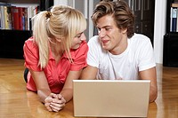 Young couple using laptop on the floor