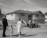 Rear view of couple and their daughter looking at nearly completed house