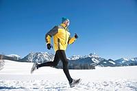 Man jogging in snow, Tannheimer Tal, Tyrol, Austria