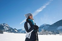 Smiling woman with nordic walking poles in winter landscape, Tannheimer Tal, Tyrol, Austria