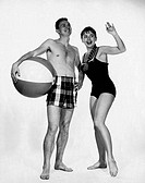 Young man holding a beach ball with a young woman waving