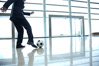 Businessman kicking soccer ball in lobby (thumbnail)