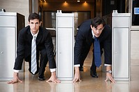 Businessmen crouching in starting position in lobby turnstiles (thumbnail)