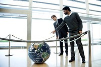 Businessmen looking at ball in lobby (thumbnail)