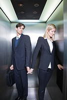 Professionals holding hands in elevator
