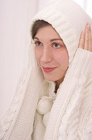 Young thoughtful woman in white woolen hood on her head, with her hands on her ears