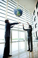 Businessmen catching ball in lobby
