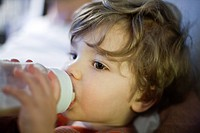 Toddler boy drinking milk from baby bottle