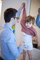 Father helping toddler boy undress