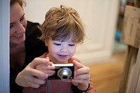 Mother and toddler son looking at digital camera together