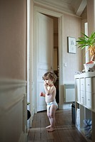 Toddler boy standing in hall, eating a snack