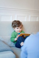Toddler boy sitting on couch with book in hands