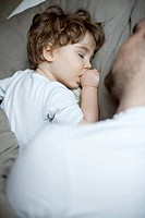 Toddler boy sleeping beside father, cropped