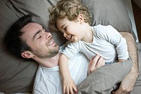 Father and young son relaxing together in bed, portrait (thumbnail)