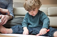 Toddler boy sitting on floor with father, drawing on paper