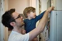 Toddler boy helping father using microwave