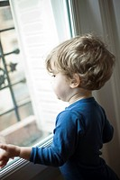 Toddler boy looking out window