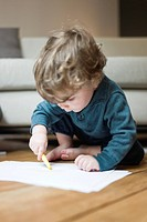 Toddler boy drawing on paper