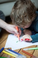Toddler boy and parent drawing together on paper