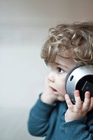 Toddler boy listening to music with headphones, portrait
