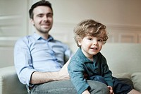 Toddler boy and father sitting on couch