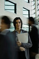 Businesswoman standing in busy lobby, portrait